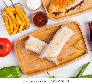 Turkish lavash doner kebab with frech fries in basket and fresh vegetables.