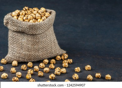 turkish leblebi, famous nut, stack of  yellow roasted chickpea in burlap sack on wooden rustic background, roasted chickpeas