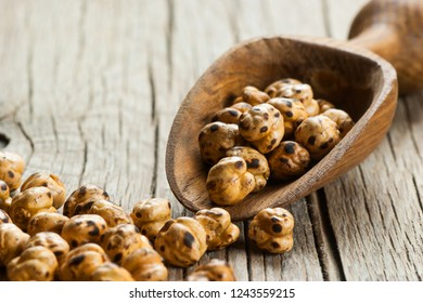 turkish leblebi, famous nut, stack of yellow roasted chickpea in wooden shovel on wooden rustic background, roasted chickpeas