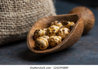 turkish leblebi, famous nut,  yellow roasted chickpea with burlap sack and wooden shovel on wooden background , roasted chickpeas