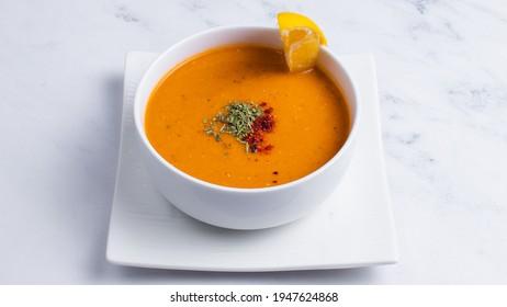 Turkish lentil soup with lemon slice isolated on white.