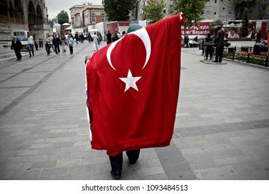Turkish man walks as he wear Turkish national flag in Istanbul, Turkey on May 28, 2015