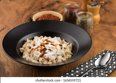 Turkish manti with pepper on wooden table