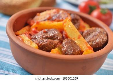 Turkish meatball kofte with potato under tomato sauce. Selective focus