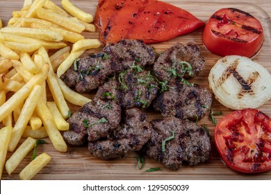 Turkish meatballs, (Turkish Food Kofte or Kofta) with red peppers,tomato, french fries and onion on a wooden chopping board.