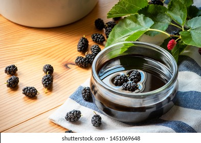 Turkish mulberry confiture pekmez and mulberries on a wooden table