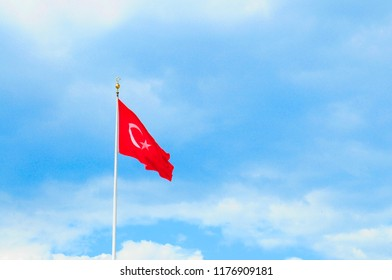Turkish national flag waves in the breeze against the blue sky background