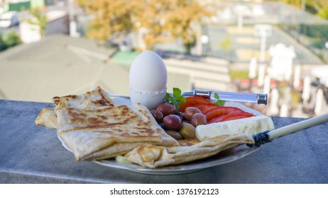 Turkish pastry food Gozleme or Borek with olives, tomatoes, cheese and egg. Breakfast plate with traditional Turkish food as known flatbread gozleme.