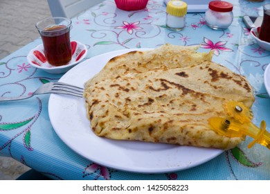 Turkish pastry food Gozleme or Borek with brewed Turkish black tea. Breakfast plate with traditional Turkish food as known flatbread gozleme with cheese or mince.
