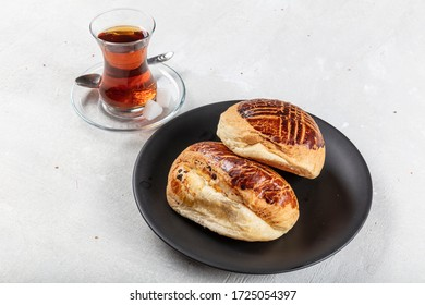 Turkish pastry product , tasty pogaca. Turkish Pastry Pogaca with Tea / Cay on wooden surface. Traditional Bakery.