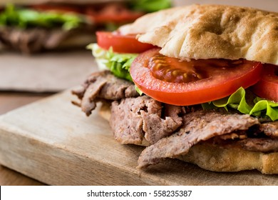 Turkish Pide Doner Sandwich with greens and tomatoes.