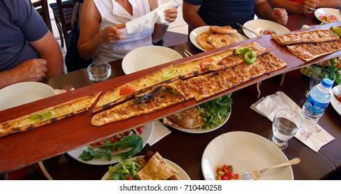 Turkish Pide pizza are served on long planks in Antalya,  Turkey