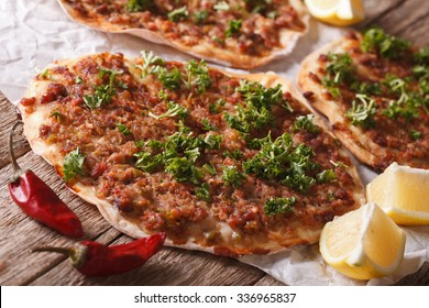 Turkish pizza with meat - lahmacun macro on a wooden table. Horizontal