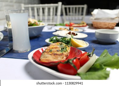 Turkish raki and Greek ouzo's feast. Tasty and healthy appetizers, grilled fish, yogurt, Roasted Peppers, olives, cheese, tomato, cucumber, herbs in the Aegean region.