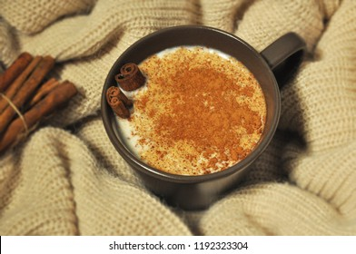 Turkish Sahlep (Salep) with cinnamon powder and sticks in brown cup.