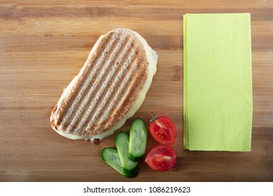 Turkish Sandwich Toast (Tost) with cheddar or melted cheese with green napkin on wooden background ,top view