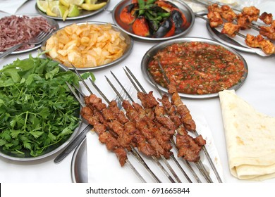 Turkish shish kebab with various salads and grilled vegetables