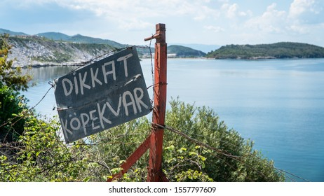 Turkish sign translating Beware of the Dog warning, on a chain link fence and sea backdrop.