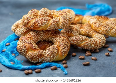 Turkish Simit Bagels with sesame seeds and coffee beans close-up on a dark textured background, selective focus.