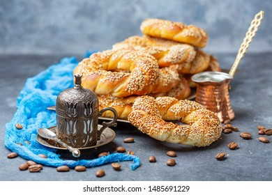 Turkish Simit Bagels,scattered coffee beans and cup of black coffee for breakfast on a dark textured background, selective focus.
