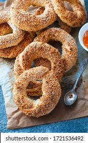 Turkish simit  homemade traditional turkish pastry. Turkish crunchy round braided bagel with sesame seeds. Served on a parchment paper with jam. Close up.
