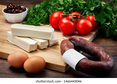Turkish string cheese on wooden table with wooden cutting board with fermanted sausage, eggs, olive, parsley and tomatoes.