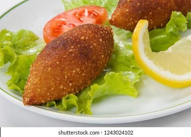 Turkish stuffed meatballs and lettuce leaves, on white plate