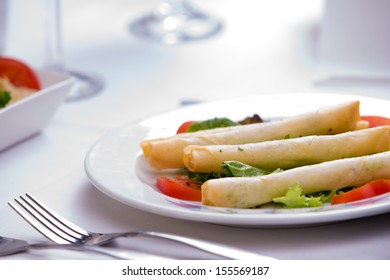 Turkish style cheese stuffed filo dough rolls served along with tomatoes and lettuce