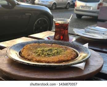 Turkish sweet -künefe on a metal dish on a wooden tray and Turkish tea in a traditional cup