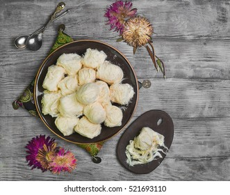 Turkish sweetness of sugar halvah pishmanie. Cloth for Turkish sweets, decorative dried flowers. Portion Turkish sweets halva pishmanie on the board. Light white wooden background. Top view. Flat lay.