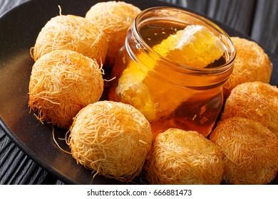 Turkish sweets balls kadaif with fresh honey close-up on a plate. horizontal