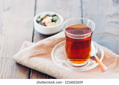 Turkish tea in authentic glass cup with delights. Closu up.