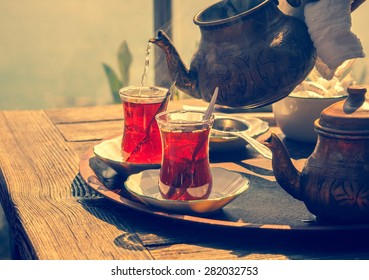 Turkish tea with authentic glass cup and copper tea kettle. Two cups of turkish tea,  toned with vintage instagram filter effect. Istanbul cafe with oriental culture of the street food.