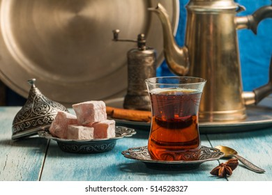 Turkish tea with authentic glass cup and copper tea kettle.