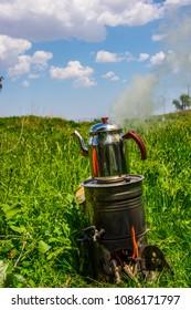 Turkish tea boiling on the grass  - Shutterstock ID 1086171797