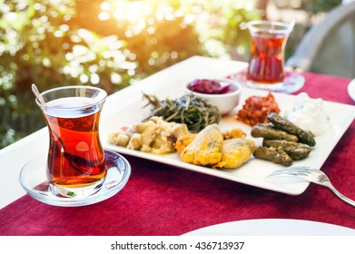 Turkish tea and meze vegetarian starter in restaurant in traditional glass on the red table in Turkey