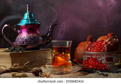 Turkish tea, the teapot is on a big book, there is steam, a national Turkish cup with tea and a vase with a ripe garnet.