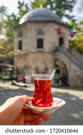 Turkish tea in a traditional turkish garden in Koza Han Silk Bazaar in Bursa, Turkey. Koza Han is historical place from Ottoman. Hand holding glass of tea with Koza Han at background - Shutterstock ID 1720410646