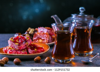 Turkish tea in traditional glass and plate with rahat lokum. Istanbul cafe with oriental culture of the street food.Evening time.