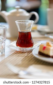 Turkish tea in traditional shape glass on table in restaurant. Close up low angle shot in sun bright light
