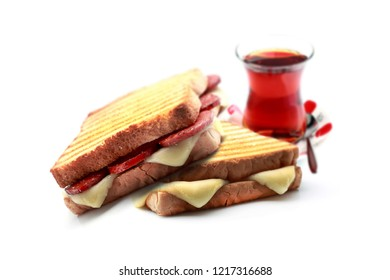 "Turkish toast with ""sucuk and cheese"" on white background. And Turkish tea."