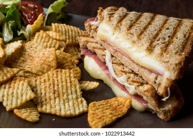 Turkish Toast or Tost / Triangle Club Sandwich with Melted Cheese, Ham and Served with Chips and Salad.