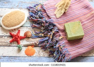 Turkish towel peshtemal with seashells, sponge, natural soap, and brush scrubber