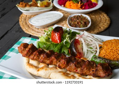 Turkish and Traditional Adana Kebab serving with salad, onion, pepper and bulgur on rustic black wood table. Dark photography concept with copy space.