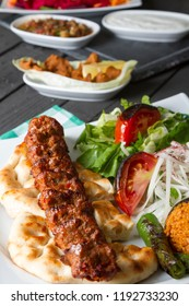 Turkish Traditional Adana Kebab serving with salad, yogurt, onion, pepper, bulgur and parsley on rustic black wood table. Dark photography concept with copy space.