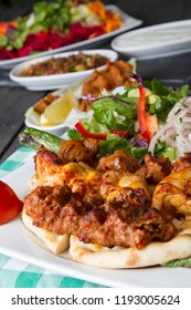 Turkish Traditional Adana, Lamb and Chicken Kebab serving with salad, yogurt, onion, pepper, bulgur and parsley on rustic black wood table. Dark photography concept with copy space.