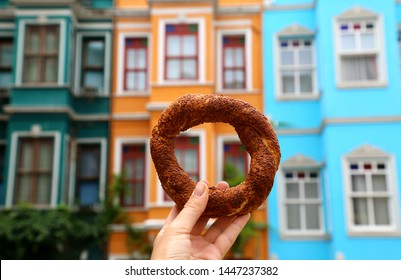 Turkish traditional bagel Simit in Balat district in Istanbul. Hand holding bagel on the colourful houses background.