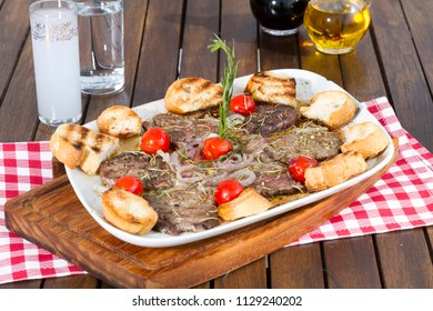 Turkish Traditional Beef Kebab with butter sauce, toasted bread, onion, tomato, green pepper and Raki or Ouzo serving on rustic dark brown wood table background.  Copy space for text area.