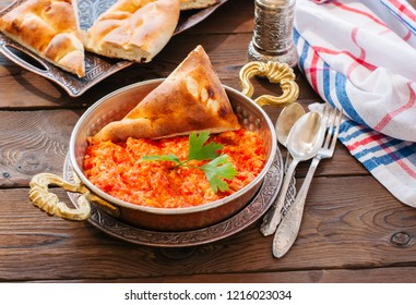 Turkish traditional breakfast - Menemen with scrambled egss, tomatoes on a wooden background.