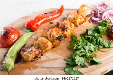 Turkish Traditional Delicious Chicken Kebab with vegetables on wood board ready to eat. White marble background.